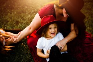 mommy and daughter laughing during fall family pictures in powder springs ga